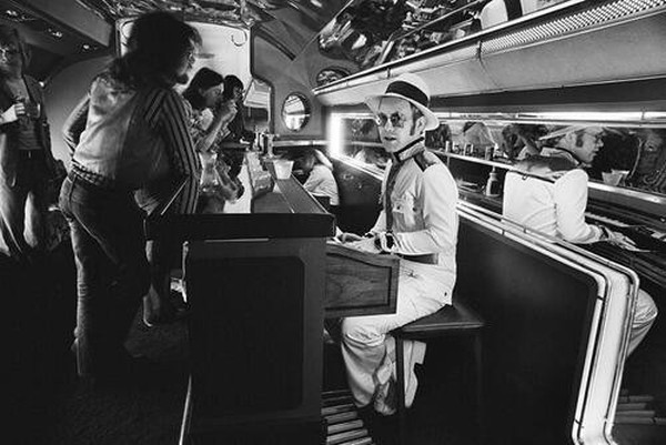 Elton John at the piano bar aboard his private plane - 1976