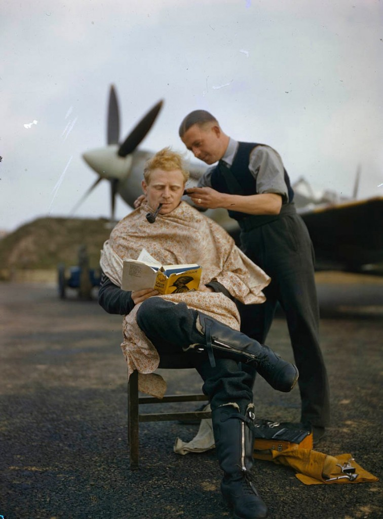 An RAF pilot getting a haircut while reading a book between missions.