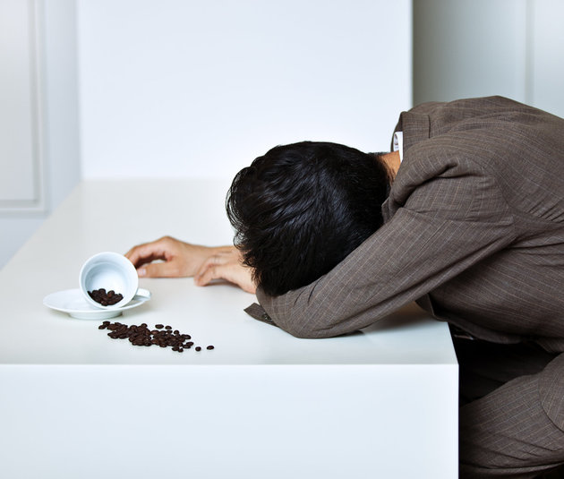 Sleeping Japanese businessman at office with a cup of coffee